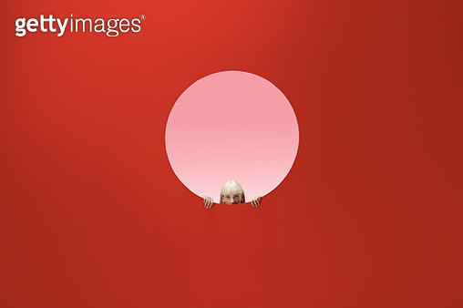 Woman peeking out of round opening in coloured wall - gettyimageskorea