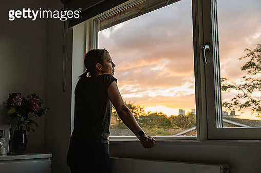 Woman looking out of window at sunset - gettyimageskorea