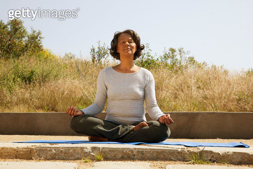 Mixed race woman practicing yoga outdoors - gettyimageskorea