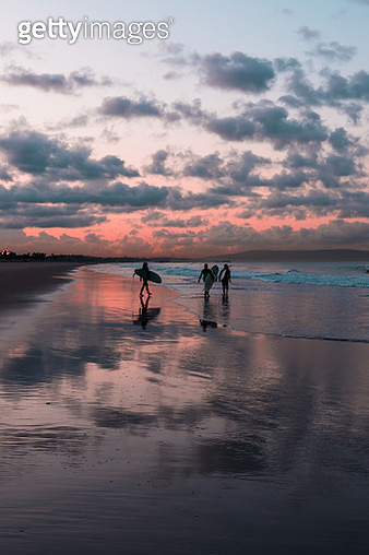 Silhouette Friends Carrying Surfboards While Walking On Shore At Beach During Sunset - gettyimageskorea