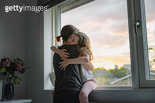 Young girl getting a big cuddle from her mother - gettyimageskorea