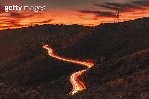 Mountain road with car light trails in incredible sunset sky. - gettyimageskorea