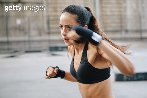 Young woman boxing in urban setting - gettyimageskorea