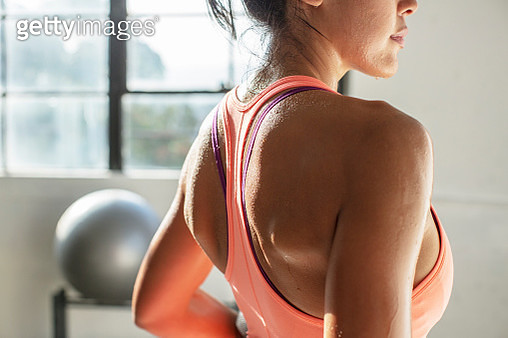 Midsection of female athlete standing in gym - gettyimageskorea