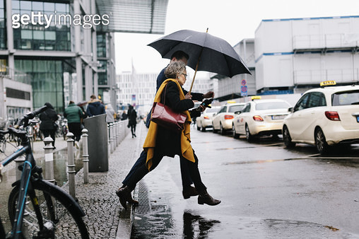 Business Associates Running For Cab In Rain - gettyimageskorea