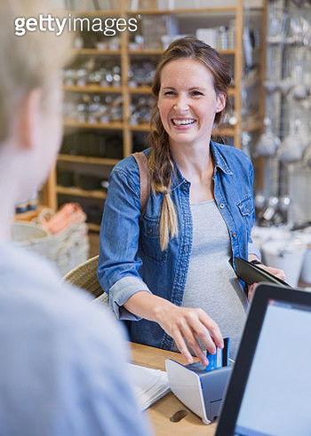 Laughing female customer using credit card machine at store checkout counter - gettyimageskorea
