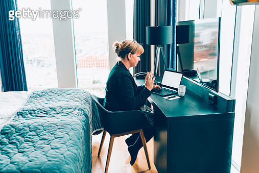Woman uses webcam on laptop to connect to people during business trip - gettyimageskorea