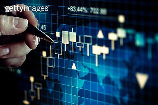 Businessman alalysing stock market graph - gettyimageskorea