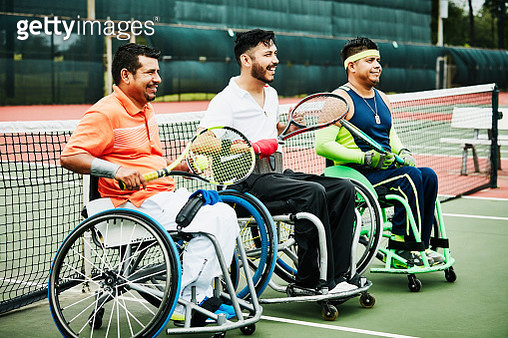 Three smiling adaptive athletes at net after wheelchair tennis match - gettyimageskorea
