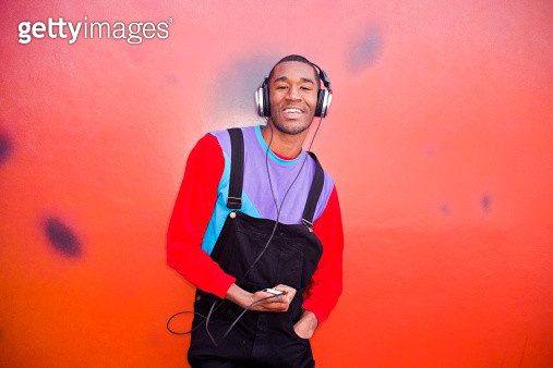 A young man dancing outside with headphones. - gettyimageskorea