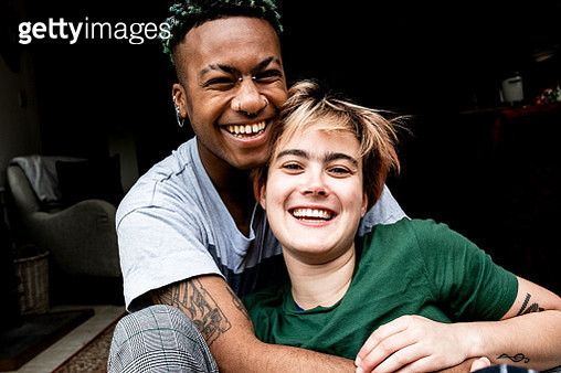 A young LGBT couple laughing and hugging - gettyimageskorea
