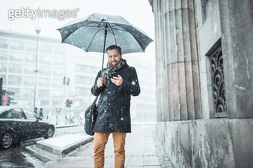 Ginger businessman standing on office building entrance, using mobile phone. Snow is falling, It's a cold winter time.  Belgrade, Serbia, Europe - gettyimageskorea
