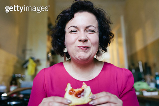 A woman smiling while enjoying her breakfast of jam on toast. - gettyimageskorea