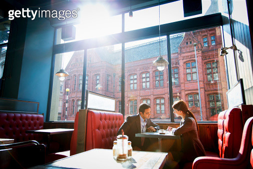 Couple sitting in restaurant booth - gettyimageskorea
