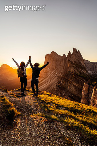 Two happy tourists greetings sunrise in mountains - gettyimageskorea