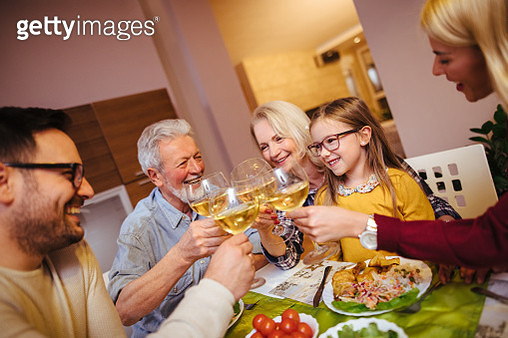 Multi-generation family toasting with white wine at home - gettyimageskorea