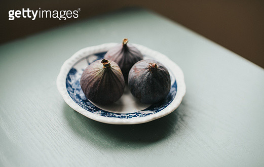 Three ripe figs on a green table on a vintage plate. - gettyimageskorea