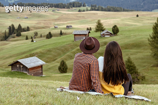 Young couple sitting and looking at Superb morning scene of Compaccio village, Seiser Alm or Alpe di Siusi location, Bolzano province, South Tyrol, Italy, Europe. Colorful summer sunrise of Dolomiti Alps. - gettyimageskorea