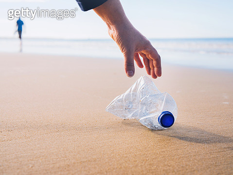 Hand picking up plastic bottle at beach. - gettyimageskorea