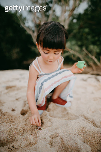 Cute little girl catching hermit crab on beach - gettyimageskorea
