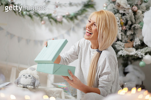 Woman in pajamas holding gift box pleased with her Christmas present - gettyimageskorea