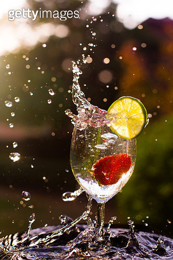 Photograph of splashing cocktail with lime and strawberry - gettyimageskorea