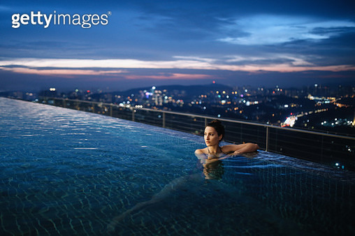 Young brunette woman relaxing in the pool, swimming on top of the building in Kuala Lumpur, Malaysia. She is having a moment to relax after work in the busy city of Kuala Lumpur, Malaysia. - gettyimageskorea