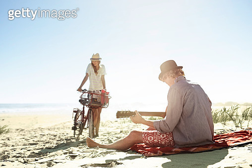 Young couple on the beach, he plays guitar. - gettyimageskorea