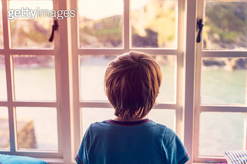 A young boy looking out of the window of a cottage by the coast. - gettyimageskorea