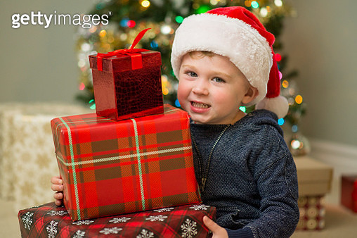 Cute little three year old boy wearing a red Santa hat sitting in front of a brightly lit and decorated Christmas tree with wrapped Christmas presents in his lap in a living room apartment. - gettyimageskorea