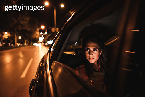 Beautiful woman sitting on back seat and looking through window at night - gettyimageskorea