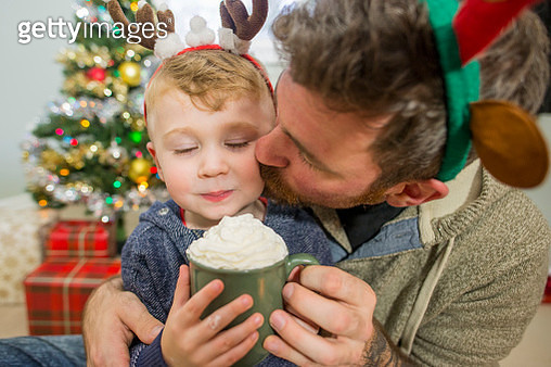 Cute little three year old boy wearing a festive reindeer antler headband getting a kiss on the cheek from his father as they share a mug of hot chocolate with whipped cream on top. They are sitting in front of a Christmas tree in the living room of their - gettyimageskorea