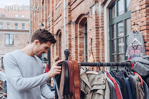 A handsome young adult man looking for second hand clothes at a flea market - gettyimageskorea
