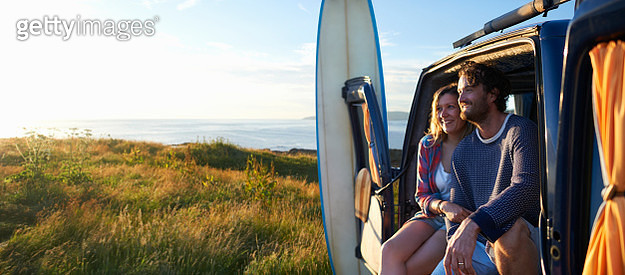 A surfing couple smile as they sit in their camper van and embrace on an idyllic summer Atlantic coastline. - gettyimageskorea