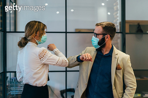 Colleagues in the office practicing alternative greeting for safety and protection during COVID-19 - gettyimageskorea