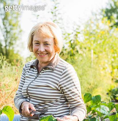 Portrait of smiling senior woman in garden - gettyimageskorea