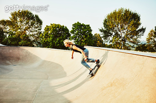 Female skateboarder skating bowl in skate park on summer morning - gettyimageskorea