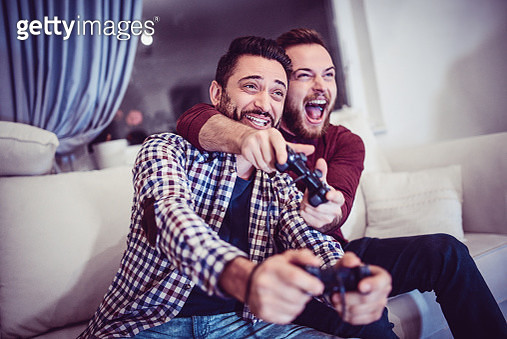 Two Excited Friends Playing Video Games - gettyimageskorea