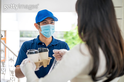 Food Delivery, Takeout Service, Cashless Society. Shot of Courier delivery food and drink to customer in front doorstep. - gettyimageskorea