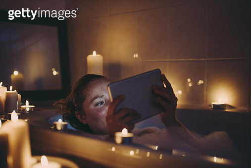 Smiling woman using tablet pc in bathtub with candles around. - gettyimageskorea