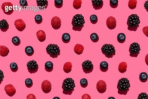 Pattern of raspberries, blueberries and blackberries against pink background - gettyimageskorea