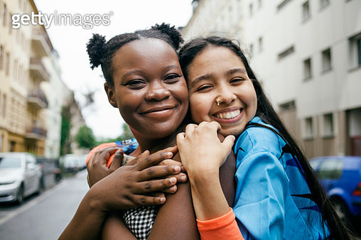Smiling affectionate lesbian couple embracing on a city street. Part of the LGBTQ Portrait series. - gettyimageskorea