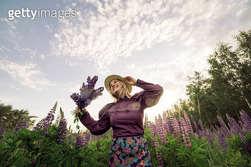 Beautiful fair-haired middle-aged woman in a lilac dress with a bouquet of lupins in her hands - gettyimageskorea