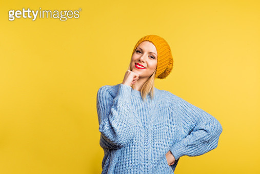 Portrait Of A Young Beautiful Woman With A Woolen Hat In Studio On A Yellow Background. - gettyimageskorea