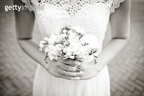 Midsection Of Bride Holding Bouquet While Standing Outdoors - gettyimageskorea