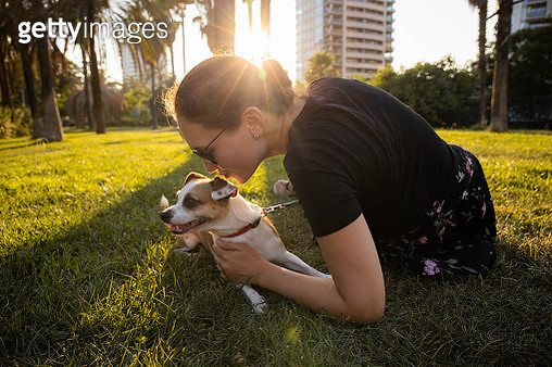 Woman giving kisses and love to her dog in the park. - gettyimageskorea