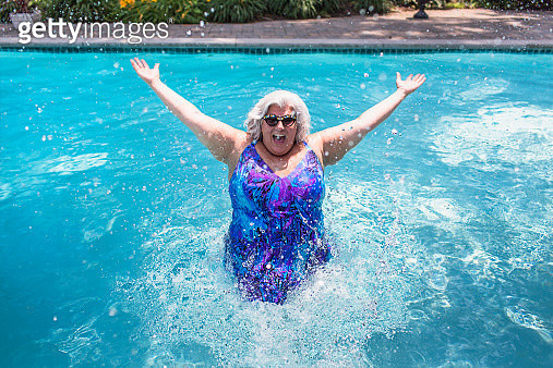 Portrait of mature woman splashing about in swimming pool - gettyimageskorea