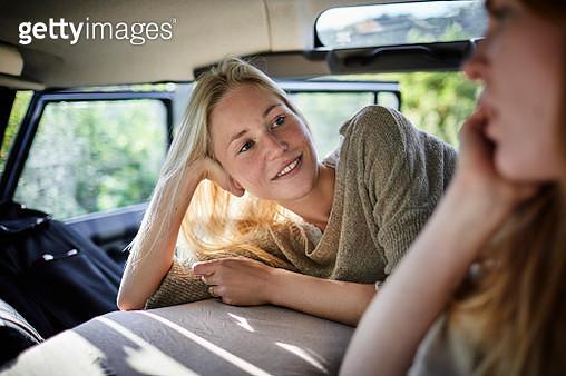 Two female friends lying on mattress in off-road vehicle - gettyimageskorea