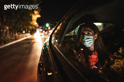 Woman wearing face mask sitting on back seat and looking through window - gettyimageskorea