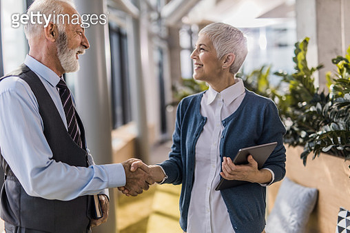Happy senior business colleagues greeting each other in a hallway. - gettyimageskorea